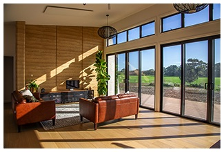 Rammed earth walls as internal thermal mass in living room